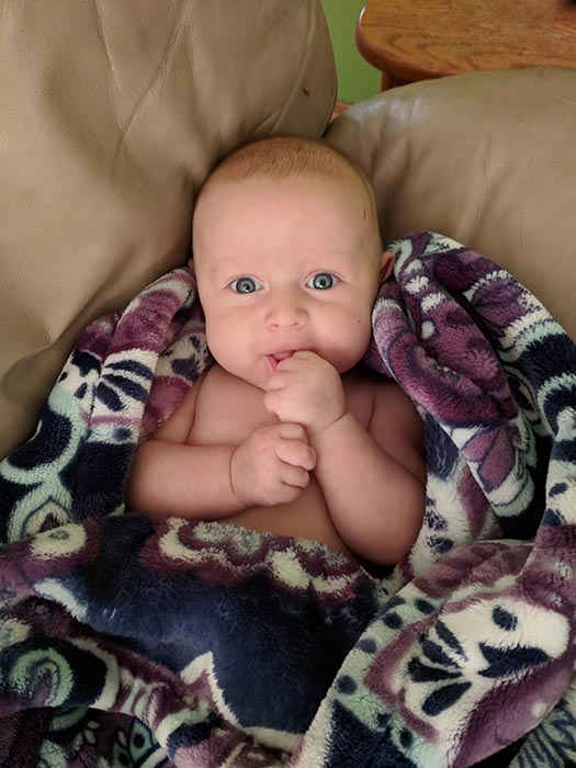 Baby Ella looking at the camera and smiling.  She is wrapped in a purple, white and blue blanket.