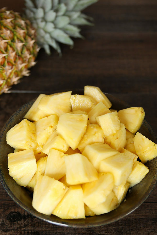 This picture shows one of the three ways to cut a pineapple in this tutorial. A pineapple sits next to a pottery bowl of pineapple chunks on a brown table.