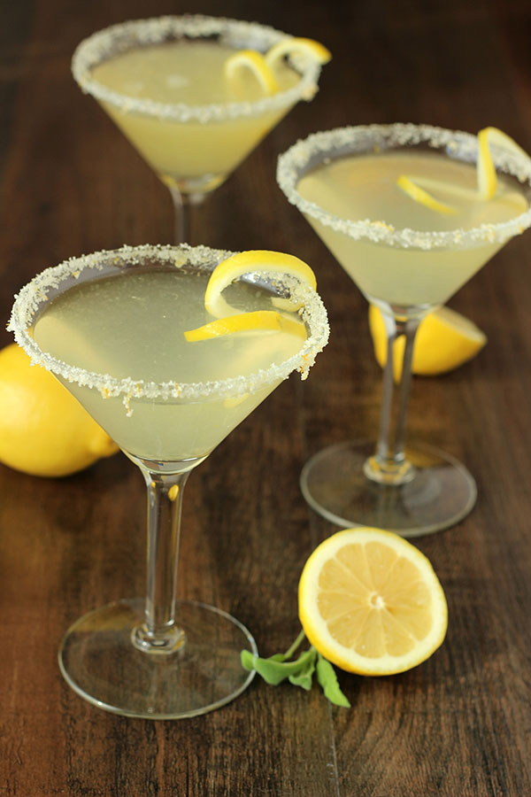 Three stunning lemon drop martinis with twists and sugared rooms. The table is decorated with a few lemons.