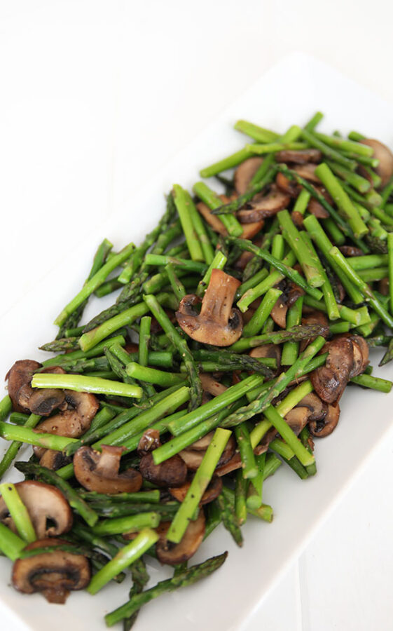 A beautiful white platter with tender spears of sauteed asparagus and caramelized slices of mushrooms