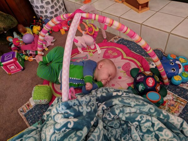 Baby Ella asleep on her play mat in Alligator pajamas.  She is surrounded by toys.