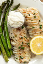 A filet of grilled cod is on a white plate next to grilled asparagus and half a fresh lemon.