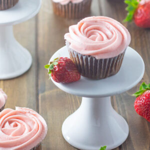 Chocolate cupcakes are frosted in fresh strawberry buttercream. One cupcake sits on a single cake stand. Additional cupcakes and strawberries are scattered around.