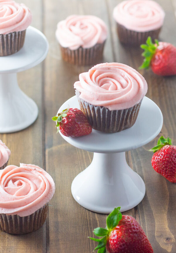 Sweet, summery strawberry buttercream is delicious swirled unto chocolate cupcakes or used for a vanilla layer cake.  These cupcakes are styled to look like pink roses with strawberry buttercream swirled unto the tops.