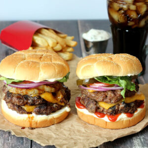 Two stunning burgers with melted cheese, condiments, fries and a coke.