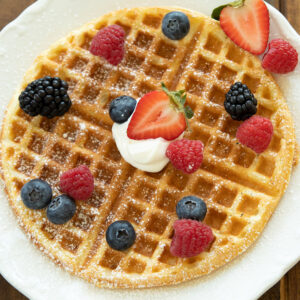 A round buttermilk waffle sits on a white plate. There are blackberries, blueberries, raspberries and strawberries on the waffle along with some whipped cream and powdered sugar.
