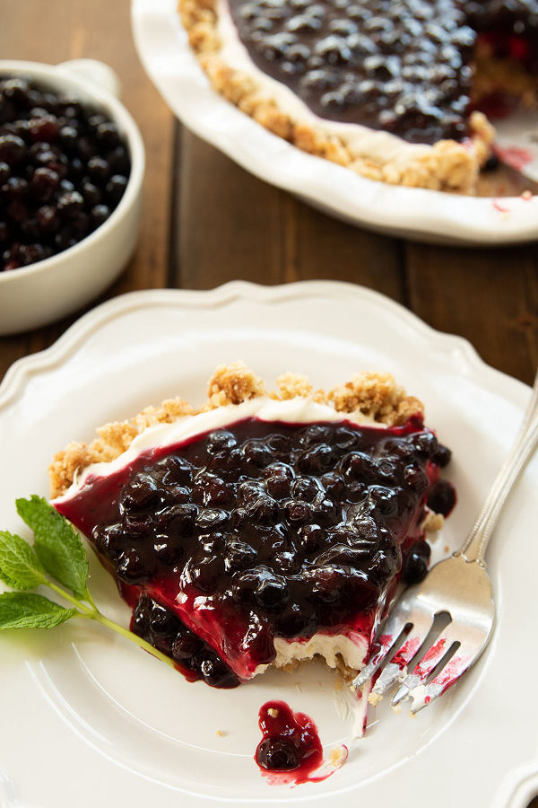 A slice of huckleberry cheesecake is plated on a white plate with a fork and a sprig of mint. You can see the rest of the cheesecake and some huckleberries in the background.