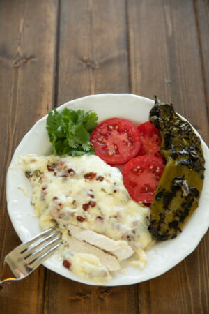 A plate of dinner features a big serving of hatch chile chicken bake, some sliced tomatoes and a whole roasted hatch chile.