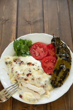 Tender chicken is slathered in a queso like cheese sauce full of bacon and hatch chili. Served with cilantro, tomato slices and an additional fire roasted hatch chili.
