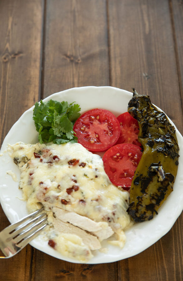 Tender chicken breast is smothered in a creamy sauce full of fire roasted hatch chile peppers.  I served this with cilantro and fresh tomato slices from my garden but it is also great with rice and beans!