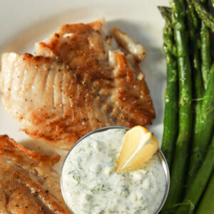 A big white dinner plate is full of tartar sauce, fried fish, and spears of asparagus. There is a wedge of lemon in the tartar sauce.