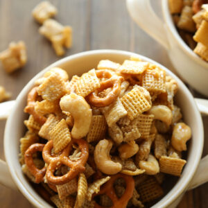 Two white bowls are full of caramel chex mix. You can see pretzels and cashews in the mixture!