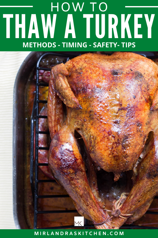 A large roasted turkey rests in a roasting rack. There is writing on the image for promotional purposes.