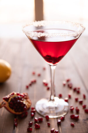 A single pomegranate martini sits on a wooden table surrounded by pomegranate seeds.