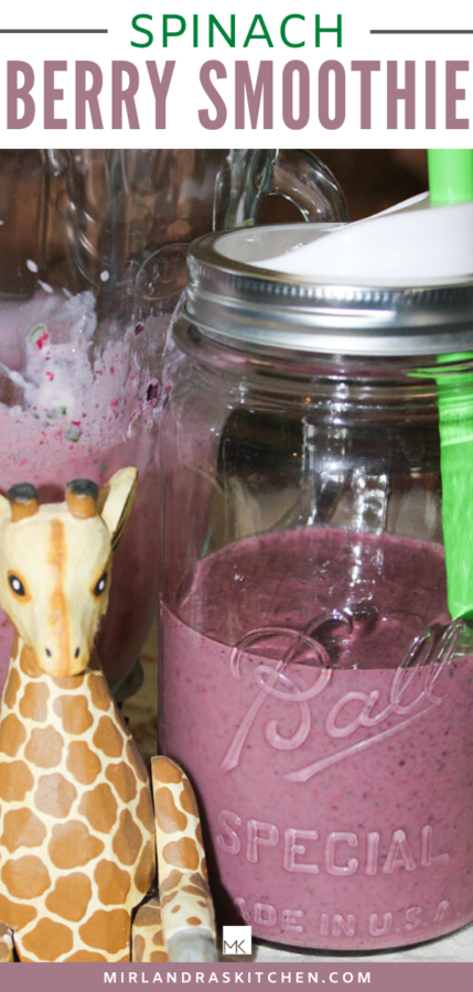 A mason jar sits on a counter next to a wooden giraffe. The jar is half through of purple, berry smoothie with a green straw in it.