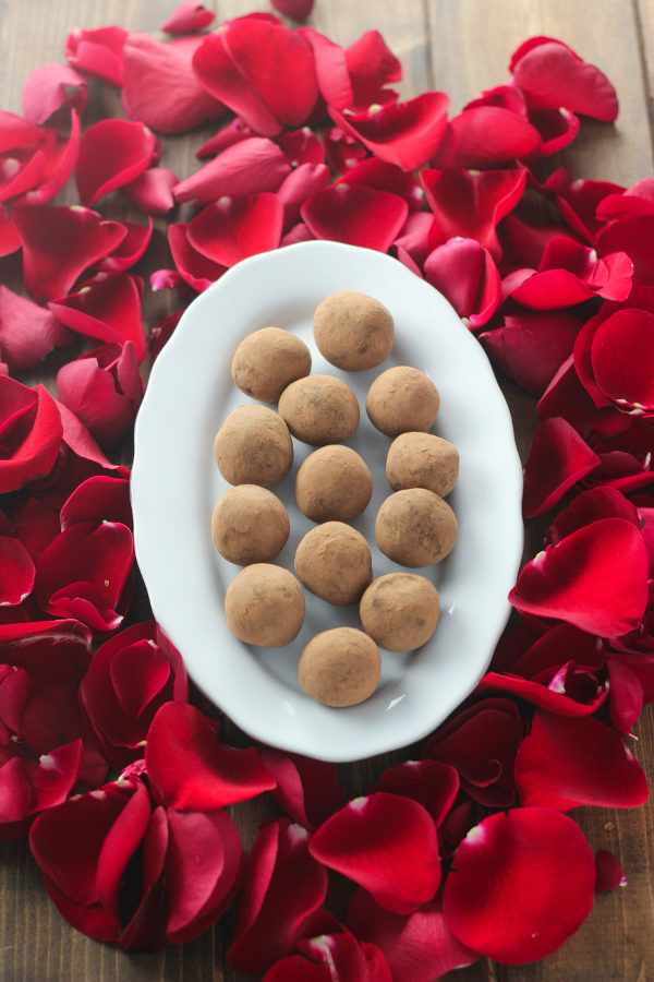 A wooden table is covered with red rose petals. In the center is a plate of hand made chocolate truffles.