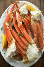 A large white platter is stacked high with steamed snow crab legs. A dusting of parsley and some wedges of lemon garnish the dish.