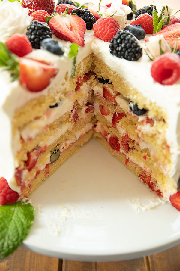 Easy Berry Chantilly Cake with a big wedge out.  Here you can see the layers of whipped cream, jam, and fresh berries.