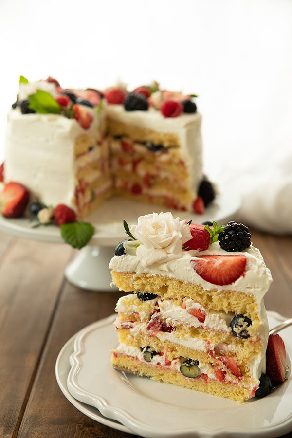 A big wedge of easy berry Chantilly cake on a white plate.  The cake is decorated with a white spray rose and fresh berries.  You can see the beautiful layers of cake and cream and berries in this photo.