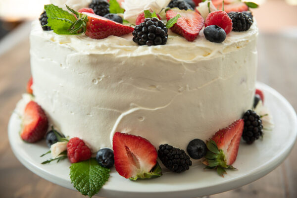 A close up of the side of a Berry  Chantilly Cake.  The frosting is spread on but not perfectly smooth.  Fresh berries make it beautiful.