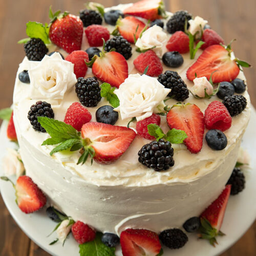 A vibrant berry chantilly cake sits on a white cake pedestal on a wooden table. The cake is covered with fresh berries and white spray roses.