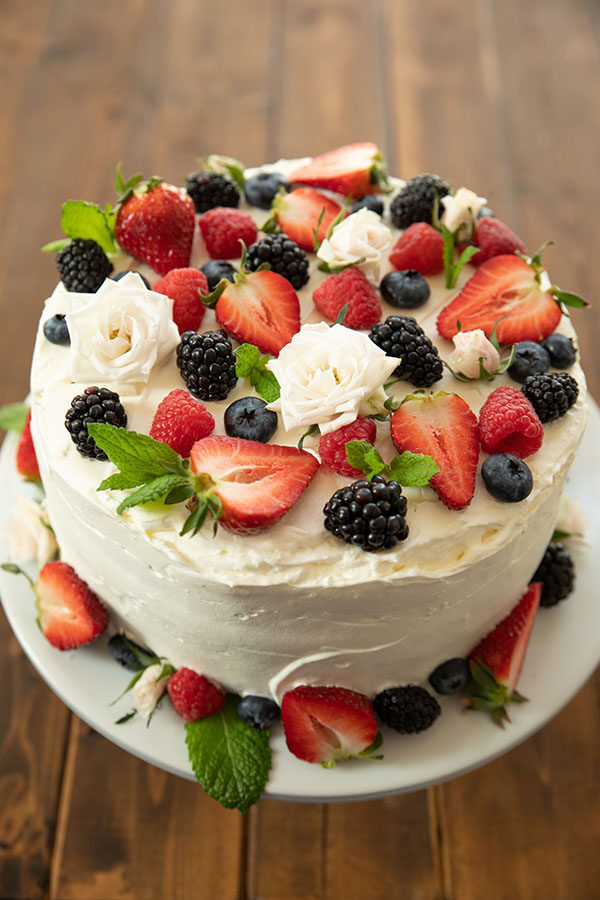A Berry Chantilly Layer cake on a white cake pedestal.  The cake is decorated with half strawberries, blackberries, raspberries, blueberries, mint leaves, and white spray roses.