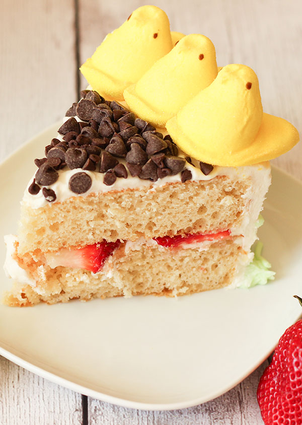A slice of peeps sunflower cake. The cake is two layers of yellow cake with strawberries in the middle. The top is decorated with chocolate chips and peeps.