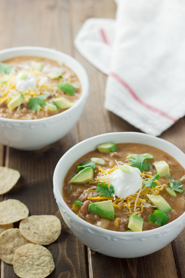 Two bowls of cheese taco soup sit on a wooden table .Each bowl is garnished with cheese, cilantro, sour cream and chunks of avocado.