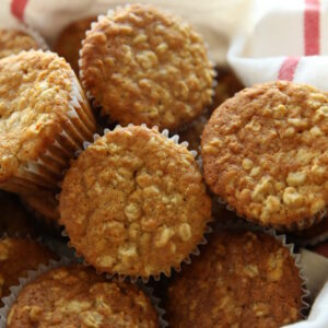 A basket is lined with a white cloth with red striped edges. It is full of golden oatmeal muffins.