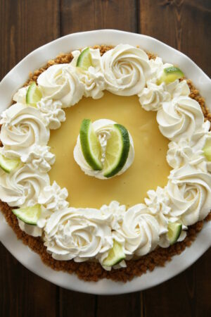 an authentic key lime pie in graham cracker crust. The whipped cream is swirled on and wedges of lime garnish the pie.