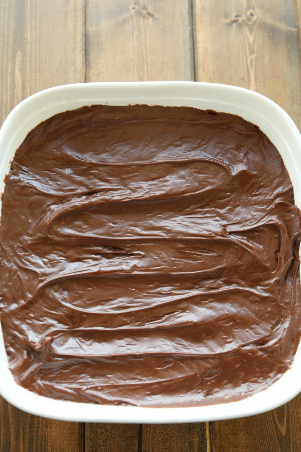 This wacky cake is a chocolate cake, frosted with chocolate frosting in a white square pan.