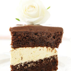 A large decadent slice of chocolate cake sits on a white plate. The cake is slathered with chocolate ganache and filled with vanilla mousse filling. There is a white rose on top of the cake.