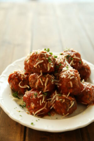 A big white plate is resting on an old fashioned wooden table. The plate is piled high with homemade Italian meatballs that are sprinkled with Parmesan cheese and fresh herbs.