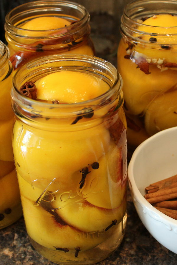 Mason jars sit on the counter next to a bowl of cinnamon sticks. The jars are being packed with peach halves and whole spices.