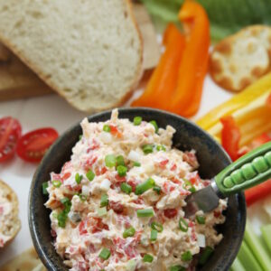 A pottery bowl of homemade pimento cheese is surrounded by saltines, celery, strips of bell pepper, crackers, lettuce, French bread, and sliced tomatoes.