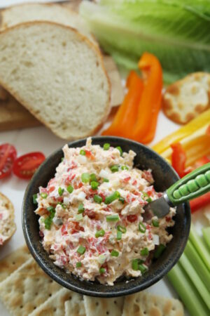A pottery bowl of homemade pimento cheese is surrounded by salteens, celery, strips of bell pepper, crackers, lettuce, french bread, and sliced tomatoes.