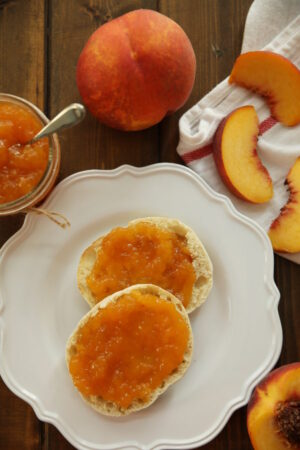 An English muffin is slathered with peach jam on a white plate. Nearby there is a mason jar of peach jam and some fresh peaches. j