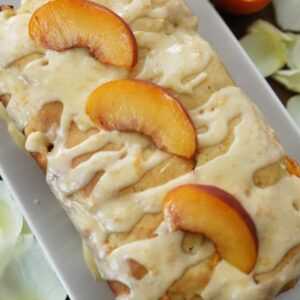 A loaf of fresh peach bread sits on a rectangular white plate. The bread is drizzled with a lot of fresh peach glaze which is a creamy yellow. Three slices of peach are on top of the bread. Next to the plate is a half a peach and some white rose petals scattered on the table.
