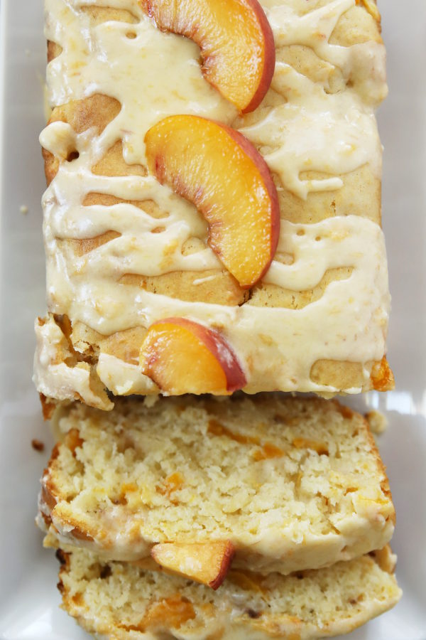 This photo is a close up of a loaf of peach bread. The first few slices have been cut and are resting at the end of the loaf. You can see the texture of the fresh peaches marbled into the bread. Slices of fresh peach sit on the glaze on top of the bread.