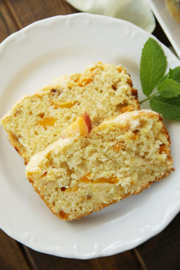 Two slices of peach bread sit on a white plate. A sprig of mint is decorating the plate. You can see the beautiful texture of the peach colored bread. The bread has a beautiful crumb studded with fresh peaches.
