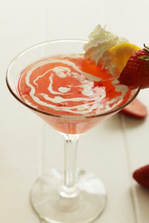 A vibrant, red strawberry martini fills a clear martini glass on a white table. The drink is garnished with heavy cream, a wedge of lemon and a strawberry.