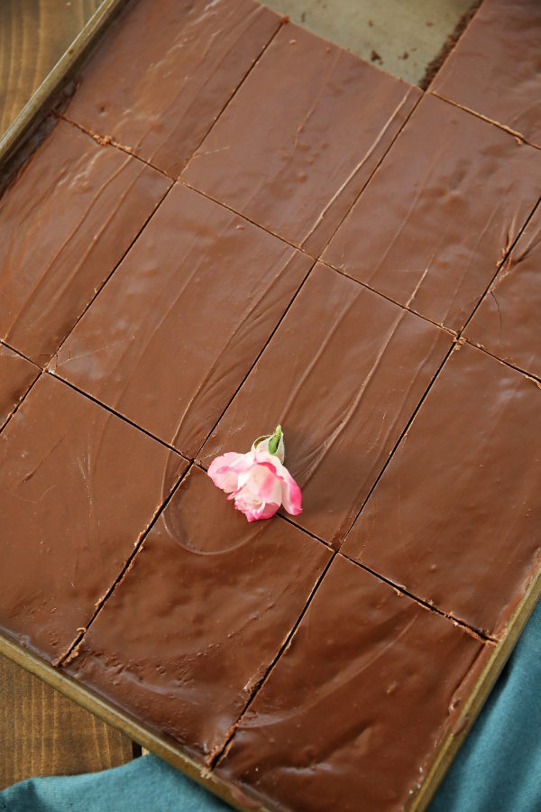 A big sheet pan of Texas Sheet cake is cut up waiting to be eaten. There is a small pink rose on top and a blue tea towel nearby