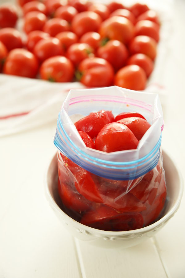 A quart ziploc bag is full of sliced tomatoes. The bag is open and sitting in a bowl while it is filled. In the background a tray of ripe tomatoes is ready for the freezer.
