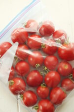 A gallon ziploc bag full of tomatoes sits on a white wooden table. The tomatoes still have stems on and are a beautiful ripe red. The bag is laying flat, ready to go to into the freezer.