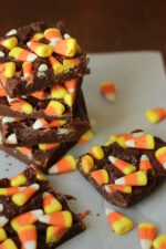 Squares of easy chocolate fudge are covered with candy corn. There is a stack of the candy corn fudge in the back with two squares of it sitting in the foreground. Candy corn is scattered around the setting.