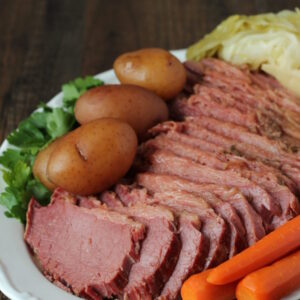 A wooden table holds a large white platter covered in corned beef dinner. There is a large corned beef sliced up, some small red potatoes, a few carrots and wedges of cabbage. The plate is garnished with parsely.
