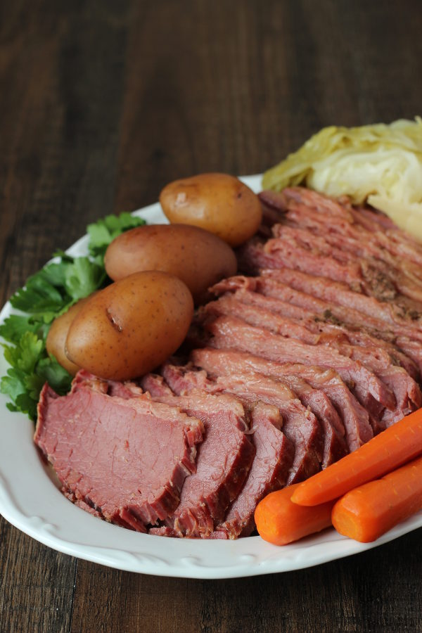 A wooden table holds a large white platter covered in corned beef dinner. There is a large corned beef sliced up, some small red potatoes, a few carrots and wedges of cabbage. The plate is garnished with parsley.