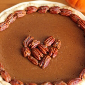A homemade pumpkin pie sits on a wooden table in a white pie pan. The pie is garnished with candied pecans around the edge and in a heart shape in the middle. There is a pie pumpkin in the background of the photo.