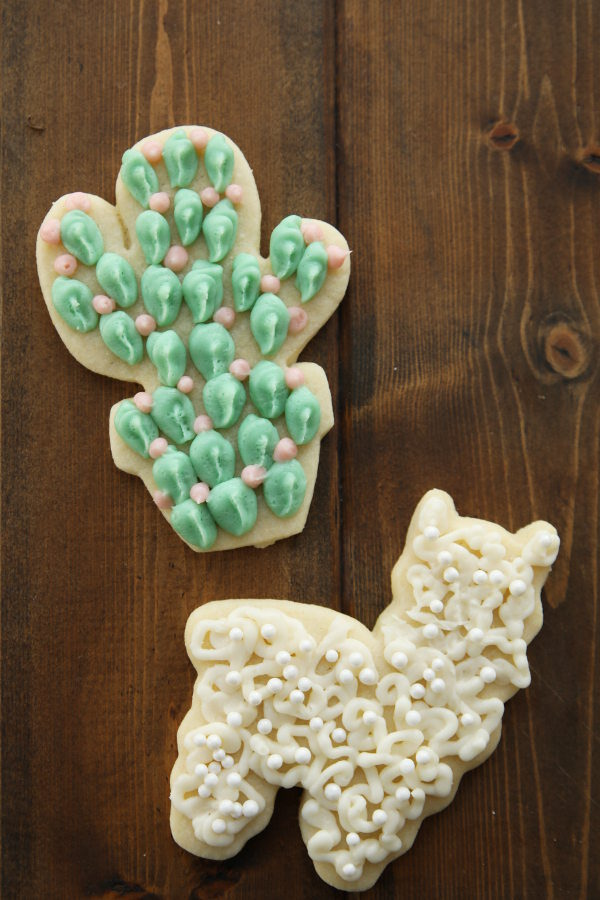 Pretty cactus and lama sugar cookies are decorated with icing and ready to be eaten. The cactus cookie has green frosting and pink flowers. The lama is decorated in white icing with pearls.