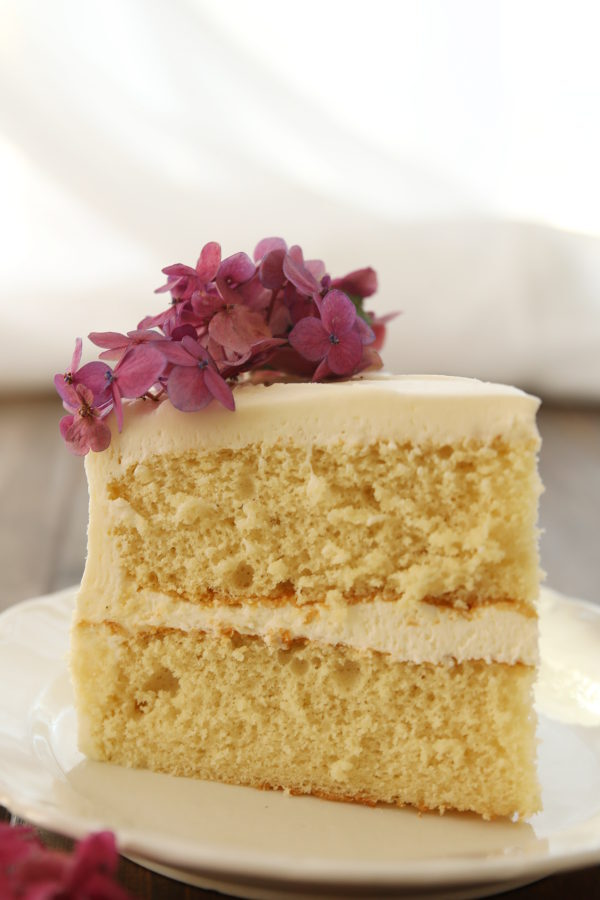 A big wedge of vanilla cake sits on a white plate. Both layers are stacked together with buttercream frosting and some purple hydrangea flowers decorate the cake on top.